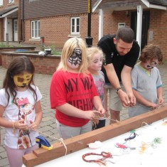 Teaching children medieval finger-braiding (also known as 'medieval friendship bracelets') at a West Kent Housing Family Fun Day in Seal