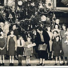 Margaret being presented with her present by Lady Anne Sackville at one of the staff Christmas parties. Margaret's mother by tree on left, Lord Charles Sackville on right of tree.