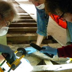 Knole Archaeology volunteers examining voids under the Knole floorboards